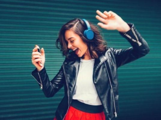 γυναίκα που χορεύει ακούγοντας μουσική από ακουστικά πρόληψη απώλειας ακοής